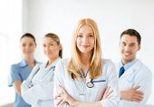 image of medicare  - attractive female doctor in front of medical group - JPG