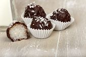 picture of bittersweet  - Three and a halved coconut milk rice with bittersweet chocolate covered truffles on wood - JPG