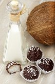 stock photo of bittersweet  - With bittersweet chocolate covered coconut milk rice truffles a coconut and a bottle of coconut cream on a wooden tra - JPG