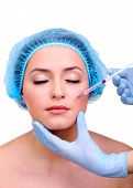 stock photo of lip augmentation  - Young woman receiving plastic surgery injection on her face close up - JPG