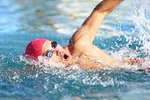 stock photo of in front  - Man swimmer swimming crawl in blue water - JPG