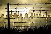 stock photo of revolt  - people are captured behind the barbed wire - JPG