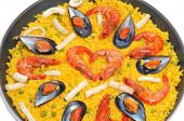 closeup of a typical spanish paella, with seafood and vegetables, in a paellera, the paella pan, on