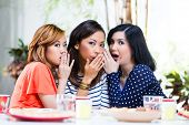 Three Indonesian friends gossip and whisper to themselves secrets in tropical environment