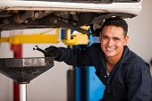 stock photo of hydraulics  - Happy young mechanic draining engine oil at an auto shop for an oil change - JPG