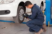 image of gun shop  - Hispanic young mechanic using an air gun to tighten the bolts of a tire from a suspended car - JPG