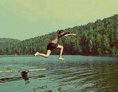 stock photo of boys  - boy jumping in lake at summer vacations  - JPG