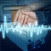 stock photo of ekg  - Hospital care and medical family support as the hand of a child giving assistance to an adult patient with an ECG or EKG icon and a stretcher as a health concept of emotional help and caring for the ailing - JPG