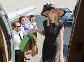 Portrait of smiling rich woman with shopping bags boarding private jet while pilot and airhostess lo