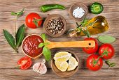 foto of homogeneous  - homemade tomato sauce in a wooden spoon on brown table and ingredients - JPG