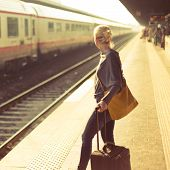 stock photo of carry-on luggage  - Blonde caucasian woman waiting at the railway station with a suitcase - JPG