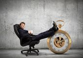 stock photo of punctuality  - Young handsome businessman sitting in chair with cup - JPG