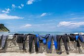 image of sky diving  - Diving suits drying on a brick wall with a sea view - JPG