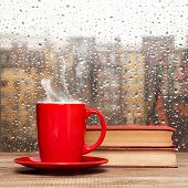 pic of rainy day  - Steaming coffee cup on a rainy day window background - JPG
