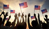 stock photo of glory  - Silhouettes of People Holding the Flag of USA - JPG