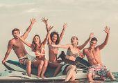 foto of ski boat  - Group of happy multi ethnic friends sitting on a jet ski - JPG