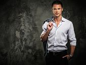 stock photo of jacket  - Handsome man in shirt against grunge wall holding jacket over shoulder  - JPG