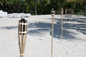 stock photo of tiki  - Decoration tiki oil torches burning outside on the beach - JPG