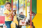 foto of carousel horse  - Cute small mixed race girl riding a colorful carousel - JPG