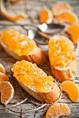 pic of baguette  - pieces of baguette with orange marmalade closeup on rustic wooden board - JPG