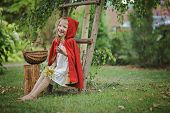 foto of little red riding hood  - Cute blonde girl playing little red riding hood in the garden, sitting by the ladder with basket and smiling ** Note: Soft Focus at 100%, best at smaller sizes - JPG