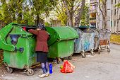 image of dumpster  - Homeless woman is searching for food in garbage dumpster - JPG