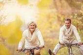 picture of bike path  - Active seniors ridding bike in autumn nature. They having fun outdoor. ** Note: Shallow depth of field - JPG