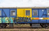 picture of covered wagon  - Old train wagon in yellow and blue covered in graffiti - JPG