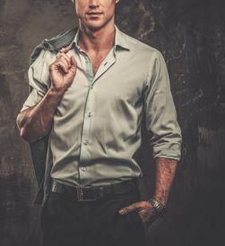 stock photo of jacket  - Handsome man in shirt against grunge wall holding jacket over shoulder  - JPG