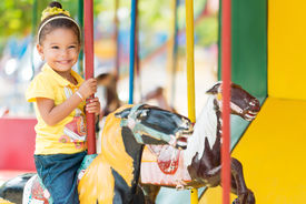 image of carousel horse  - Cute small mixed race girl riding a colorful carousel - JPG