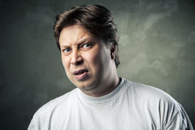 foto of disgusting  - Man with disgusted expression over dark grey background - JPG