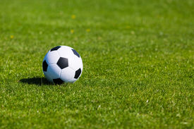 stock photo of football pitch  - Black and white soccer ball on green soccer pitch - JPG