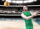 stock photo of volleyball  - Volleyball player on green uniform on volleyball court - JPG