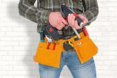 foto of hammer drill  - Manual worker holding gloves and hammer power drill against white wall - JPG