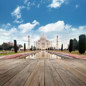 stock photo of mausoleum  - A perspective view from wooden balcony to Taj Mahal mausoleum with reflection in water - JPG