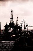 stock photo of oil drilling rig  - Oil Drilling Rig Silhouette over a Cloudy Sky - JPG