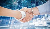 picture of handcuffed  - Handcuffed business people shaking hands against new york - JPG