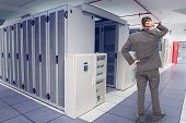 foto of inquisition  - Young businessman standing back to camera scratching his head against data center - JPG