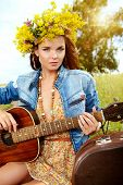 stock photo of hippy  - Romantic girl in a wreath of wild flowers playing her guitar - JPG
