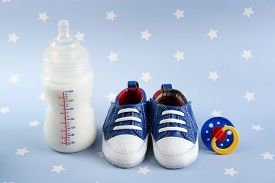 picture of nipples  - Baby shoes with nipple and bottle of milk on blue background - JPG