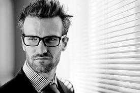 stock photo of posh  - Posh businessman in eyeglasses on background of jalousie - JPG