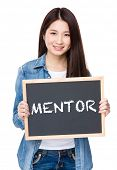 stock photo of mentoring  - Young woman hold with chalkboard showing a word of mentor - JPG