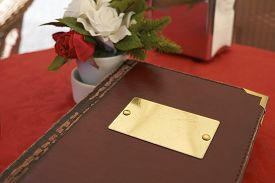 stock photo of leather-bound  - Detail of leather bound menu with blank name plate on red table cloth - JPG