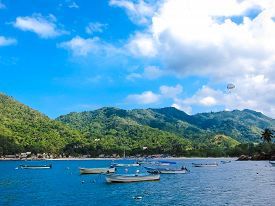 picture of parasailing  - Boats And Parasailing At Blue Mexican beach village with mountains and huts  - JPG