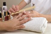stock photo of nail salon  - Manicurist filing client - JPG