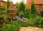image of english cottage garden  - Quaint English Cottage Garden With Chapel In the Background - JPG