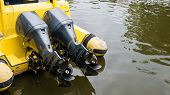 Постер, плакат: Close Up Of Two Motor Boat Engine Propellers Over Yellow Boat In Water Boat Propellers Concept With