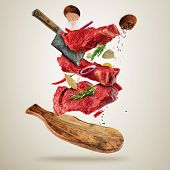 Flying pieces of raw beef steaks, with herbs, served on wooden board. Meat chopper cutting the flesh poster