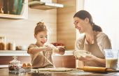 Happy loving family are preparing bakery together. Mother and child daughter girl are cooking cookie poster