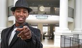 pic of opryland  - Attractive African American thirty something business man in pinstripe suit in hotel lobby pointing - JPG